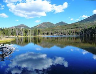 Sprague Lake in Rocky Mountain National Park. Glassy blue lake with clouds reflected and above, surrounded by forest and mountain peaks in the background. A forest area the size of RMNP is cut down twice per year to create junk mail for US households.