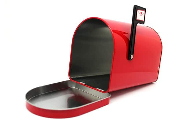 Red mailbox with door open and empty inside, containing no junk mail. Flag is raised and has icon of letter with heart stamp.