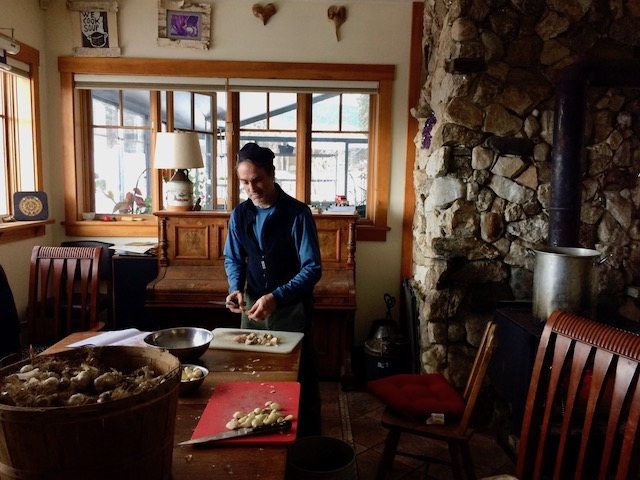 D Acres, Community Permaculture, permaculture, permaculture farm, New Hampshire farm, community kitchen, wood stove, peeling garlic