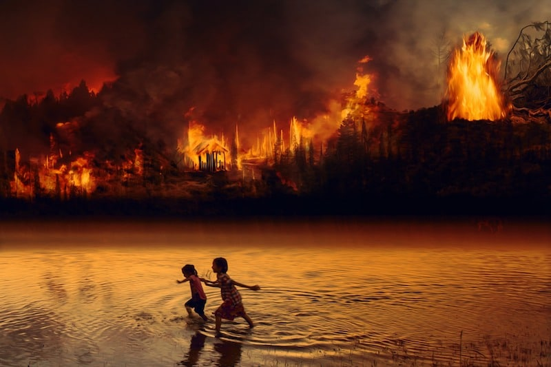 Amazon Rainforest Fires. Children in river escaping fire.